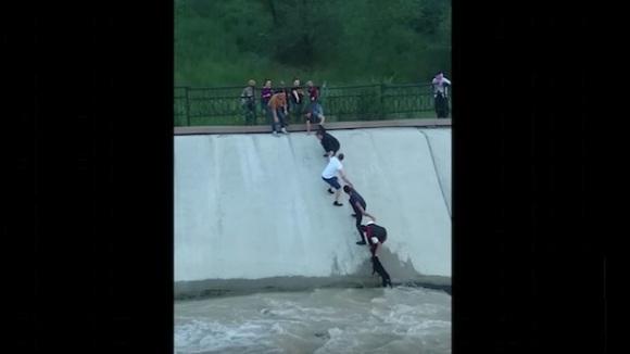 Clipul care te va ține cu sufletul la gură: au format un lanț uman, pentru a salva un câine din apele repezi ale râului – VIDEO impresionant
